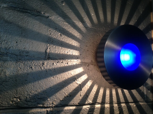 Blue light fixture with shadow and light rays streaming from sides